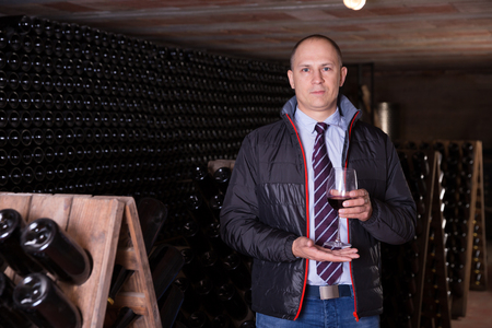 Confident winemaker inviting to wine cellar, offering glass of red wine for tasting Foto de archivo