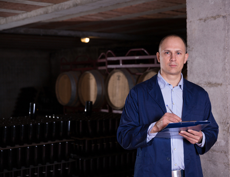 Winemaker controlling production wine in winery vault, noting in notebook