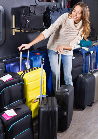 Positive female customer choosing travel suitcase in haberdashery shop