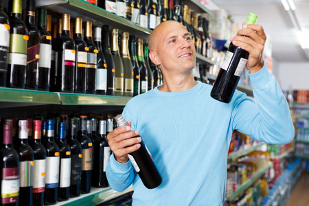 Portrait of concentrated man purchasing wine  in supermarket