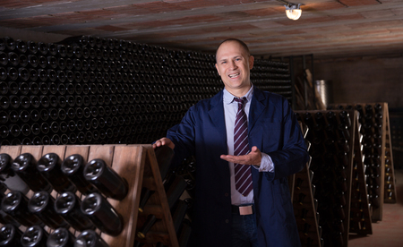Male winemaker giving tour around winery, showing wine cellar with wine bottles racks