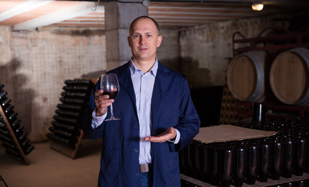 Professional winemaker conducting tour around wine cellar proposing degustation of red wine