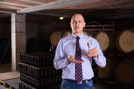Confident positive glad winemaker offering glass of white sparkling wine for tasting in wine cellar