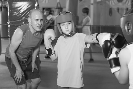 Group of kids practicing with mentor on boxing ring at gym