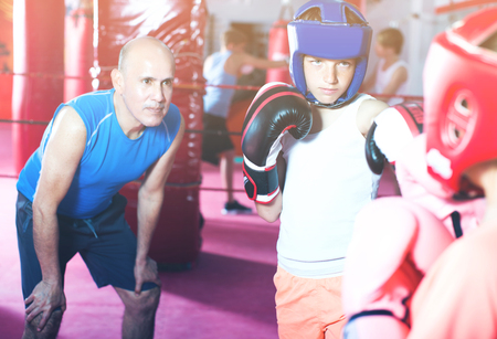 Serious boxer sparring on the ring in boxing hall Stok Fotoğraf