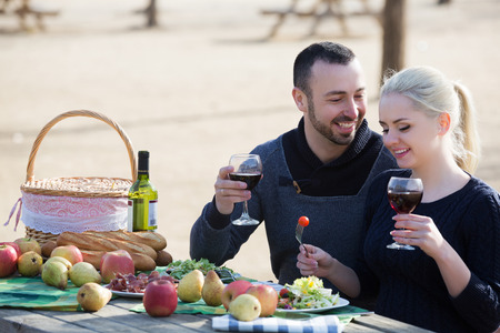 Portrait of happy young adults drinking wine at table in nature
