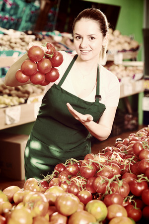 Friendly attractive saleswoman offering ripe tomatoes in supermarket