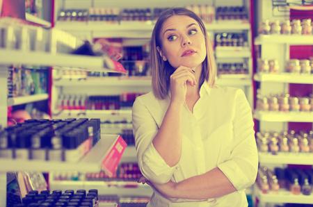 Portrait of thoughtful stylish woman in modern cosmetics store Stock Photo