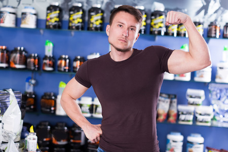 young guy  showcassng his musculature in a store with sports nutrition and supplements