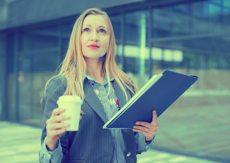 Portrait of cheerful female with documents standing outdoor drinking coffee