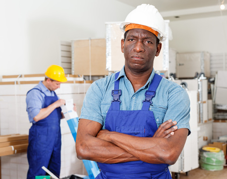 Portrait of confident African-American construction worker standing at indoors building site Imagens