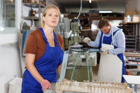 Portrait of confident young woman in blue overalls working in glass workshop