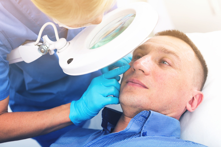 Female doctor is doing cleaning skin procedure to client in cabinet. Banco de Imagens