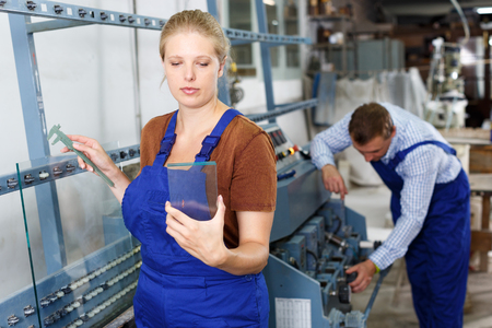 Experienced young workwoman choosing glass for cutting in industrial workshop, measuring thickness with caliper Stock Photo