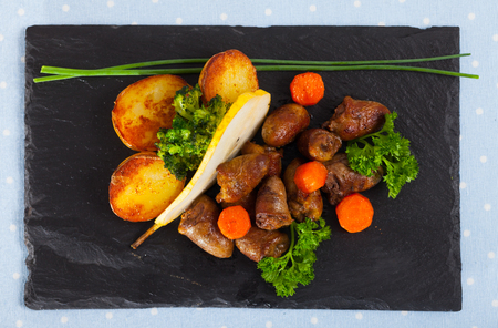 Top view of fried chicken hearts with baked vegetables and fresh pear on black serving board