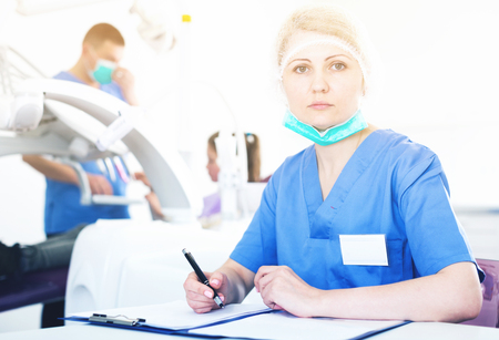 Qualified female stomatologist recording diagnosis of patient at modern dental clinic Stock Photo