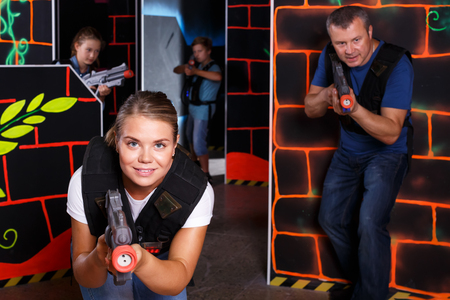 Portrait of young woman with laser pistol having fun with family on lasertag labyrinth