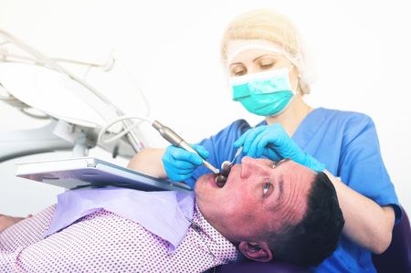 Portrait of man on dental checkup in modern dentist office