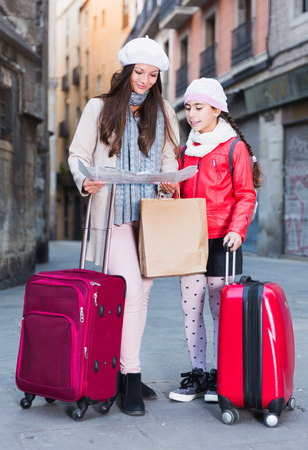 adult female and daughter in the city center in scarf with map Stok Fotoğraf
