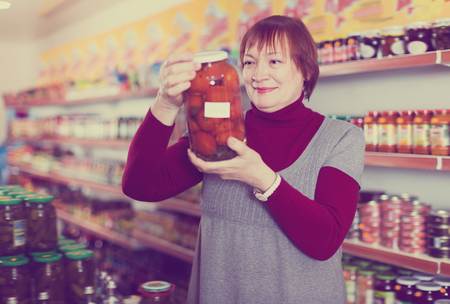 Ordinary woman buyer choosing canned jar of tomatoes at the supermarket 免版税图像 - 110014553