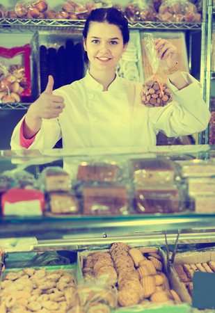 Diligent friendly woman selling  cookies and other fillings Imagens