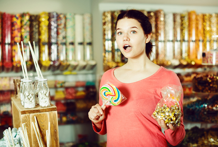 Happy brunette girl buying candies at shop
