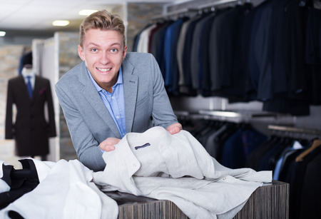 Adult male purchaser in jacket choosing shirt in the clothes store Banco de Imagens