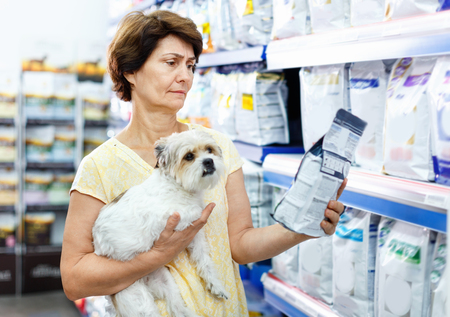 Careful cheerful  senior woman visiting pet shop in search of dry food for her dog Фото со стока