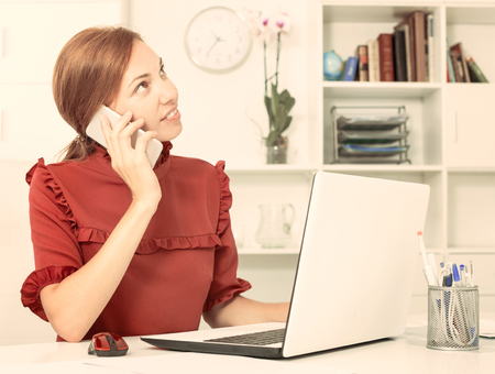 Smiling woman talking on mobile phone and working using laptop at company office