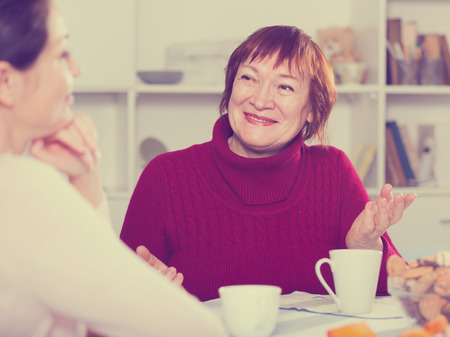 Happy adult female talking with daughter with cup of coffee at table