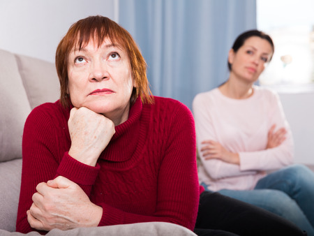 Unhappy women sitting at sofa after conflict at home interior