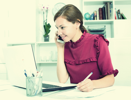 Portrait of confident happy woman working in company office with laptop and talking on phone