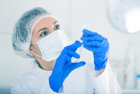 Female nurse holding syringe for injection in hospital