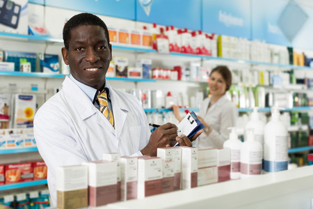 Smiling man chemist making notes on clipboard during inventory in pharmacy