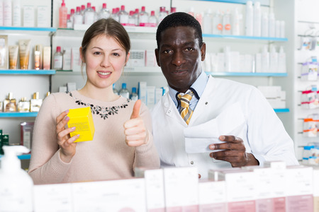 Portrait of delighted woman customer of pharmacy with confident male pharmacist