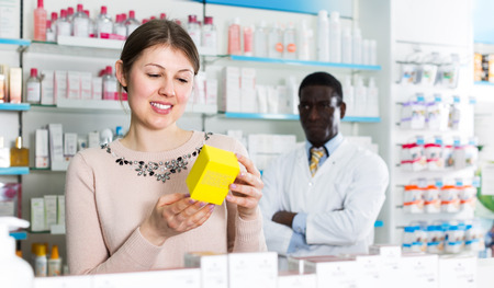 Happy female customer found necessary medicines in modern pharmacy