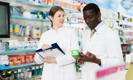 Experienced adult male and female pharmacists taking inventory of medicines in pharmacy