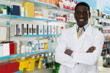 Experienced man druggist standing on background with shelves of medicines in pharmacy