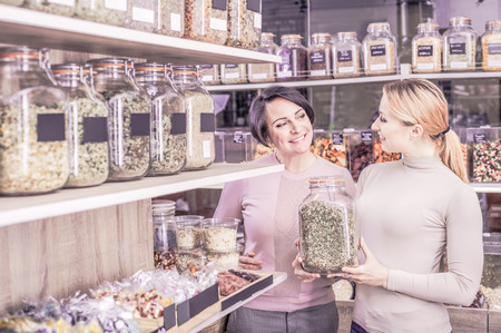 Positive young blond and adult brunette women choosing dried herbs sold by weight in organic shop. Focus on brunette