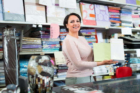 Cheerful  pleasant mature saleswoman offers  goods  in  textile shop Stock fotó