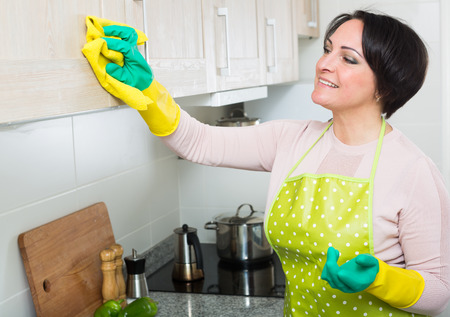 Portrait of middle aged female cleaning kitchen cupboards at home
