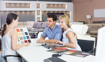Portrait of a young couple who are consulting with the assistent about the choice of a color for new sofa Stockfoto