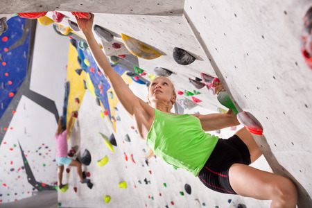 Young female alpinist practicing indoor a rock-climbing on artificial boulder without a safety belts