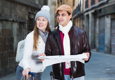 Cheerful man and woman with map and package looking attraction outdoors 免版税图像