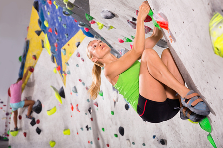 Young cheerful sporty woman training at bouldering gym without special climbing equipment