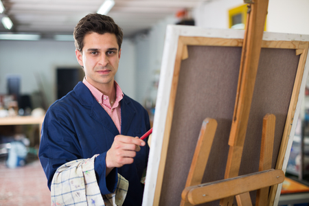 Smiling man with brush near easel painting on canvas Imagens - 110215037