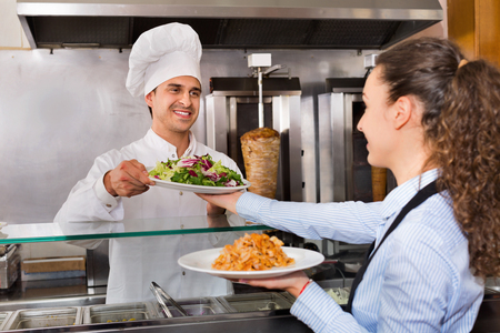Happy positive  professional chef and young waitress taking kebab for client