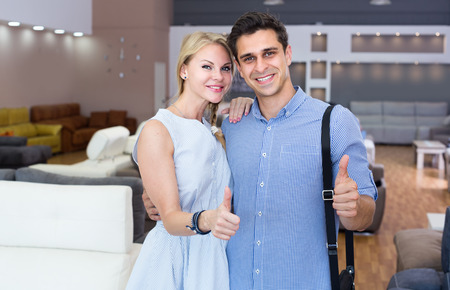 Young wife and husband are satisfied by buying new sofa in furniture store. Archivio Fotografico