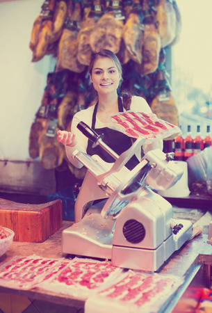 smiling european female butcher with lard and meat in counter of store Imagens