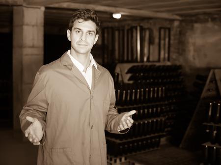 friendly man wearing uniform working with bottle storage racks in winery cellar